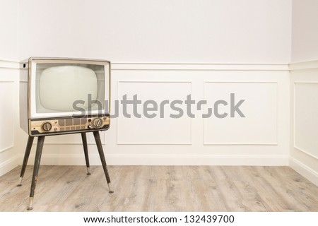 Old vintage television in the corner of cozy room, left hand space available for text or graphic - stock photo