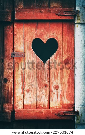 Old vintage toilet door with a heart shaped hole, filters applied - stock photo