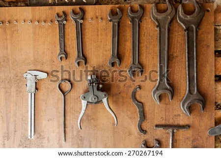 Old vintage tools hanging on a wooden clipboard, hobby time in garage. - stock photo