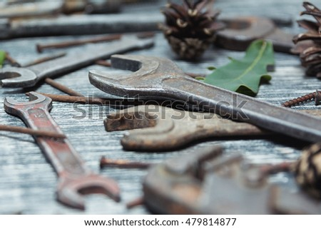 Old vintage tools on a wooden table. Different tools on a black and white wooden background