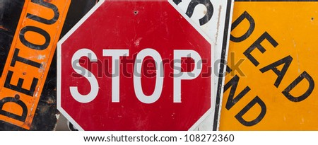 Old, vintage traffic signs including a stop sign, a detour sign, and a dead end sign making a background.  Caution theme - stock photo