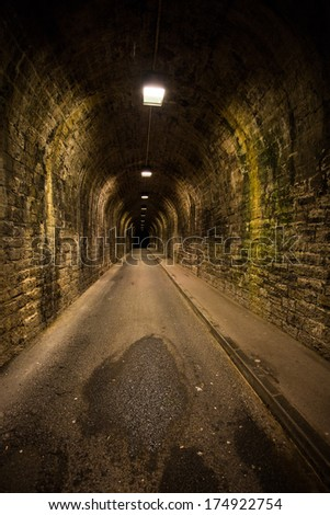 Old vintage tunnel in Biarritz at night. Long time exposure. Old bricks and humidity on the ground. - stock photo