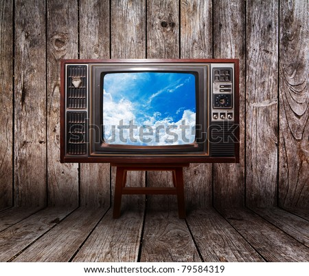 Old vintage TV in the Vintage wooden room on table with sky view
