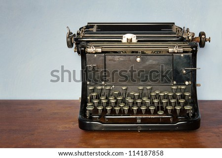 Old vintage typewriter on a rustic wooden table - stock photo