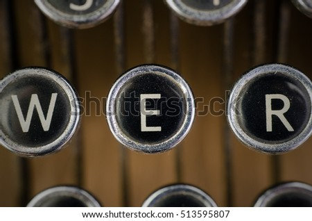 Old vintage typewriter on wooden desk. close up of black and white keys focusing on the letter E.