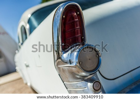 Old vintage white veteran car red rear tail light with blue sky - stock photo
