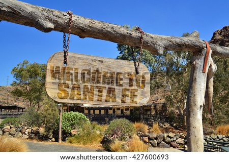 "old vintage wood signboard with text "" welcome to santa fe"" hanging on a branch"