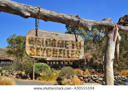 """old vintage wood signboard with text """" welcome to seychelles"""" hanging on a branch - stock photo"""