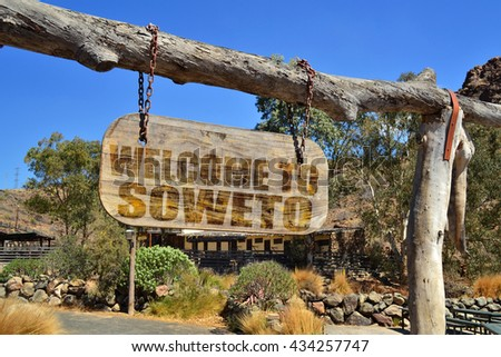 "old vintage wood signboard with text "" welcome to Soweto"" hanging on a branch"