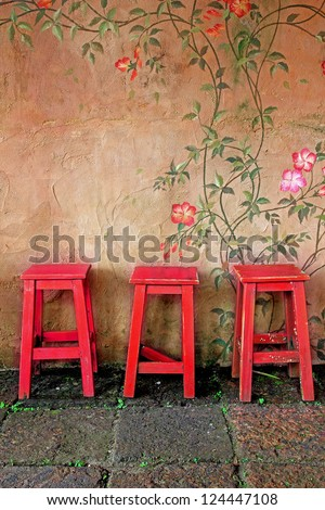old vintage wooden chair and wall - stock photo