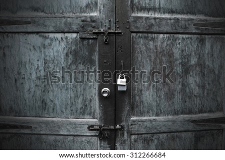 Old vintage wooden door with rusty iron lock