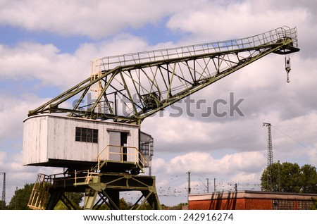 Old Vintage Wooden Port Crane on a Cloudy Blue Sky