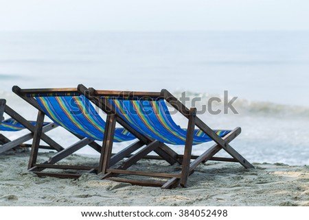 Old vintage wooden sun beds at the beach - stock photo