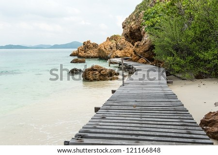 Old vintage wooden walking bridge over sea water, taken on a sunny day - stock photo