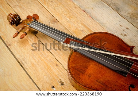 Old viola and arch on a wooden background - stock photo