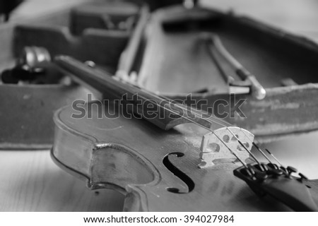 Old violin and bow laying over open worn case. Selective focus on f-holes and the bridge. Aged photo. Black and white. - stock photo