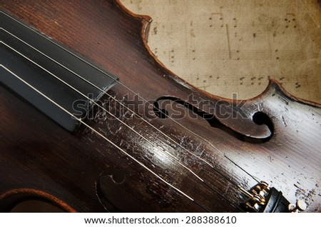 Old violin lying on the sheet of music, music concept - stock photo