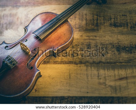 Old violin on a wooden background, stringed musical instrument