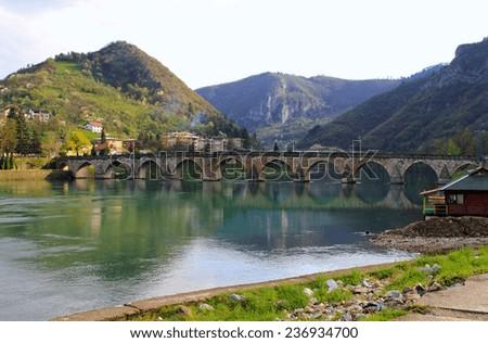Old Visegrad bridge landmark at Drina river - stock photo