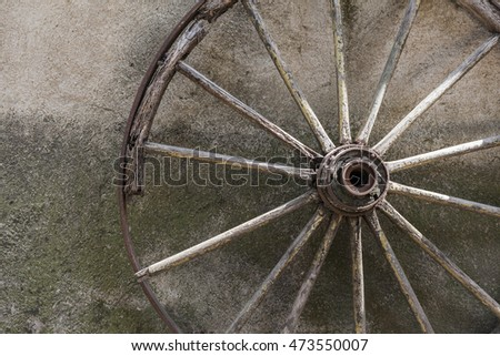 Old wagon wheel leaning against the wall.