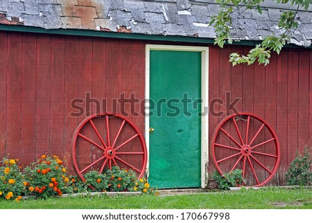 old wagon wheels by green door barn - stock photo