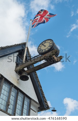 Old Wall clock with blue sky and the Union Flag on top