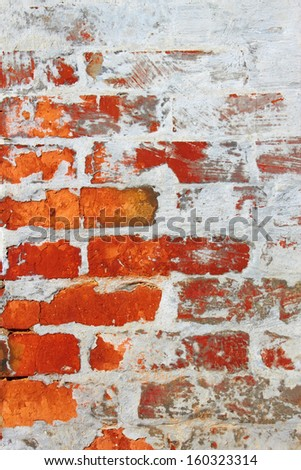 Old wall from a red brick partially covered by cement mixed with lime