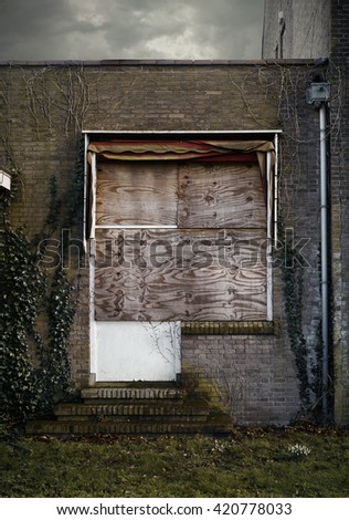 Old wall with boarded up window, door and ivy.
