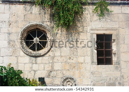 Old wall with round and rectangular windows - stock photo