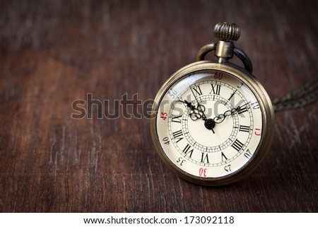 Old watch on wood table - stock photo