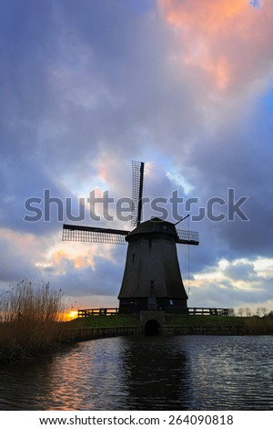 Old water mill beside a canal of the Eilandspolder in sunset, the Netherlands - stock photo
