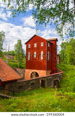 Old water powered red wooden mill on granite Foundation. Forest in background and tree trunk to the left. - stock photo