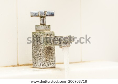 Old water rusty bathroom tap - stock photo