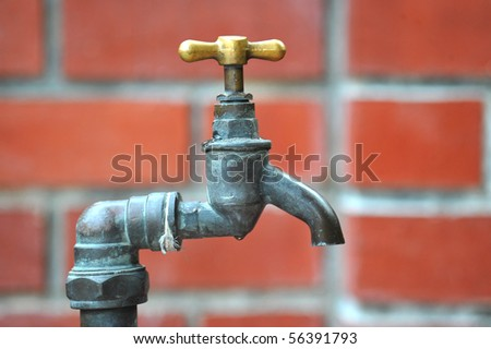 Old Water Tap Against A Brick Wall - stock photo