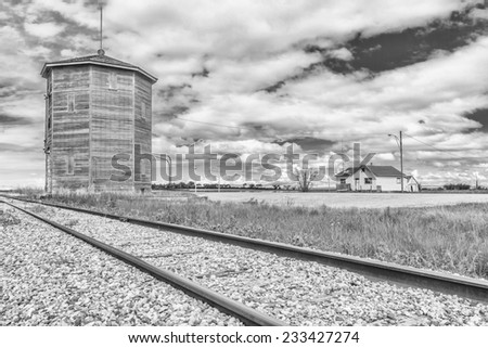 Old water tower or station along the railroad track near an old abandoned house on the prairies. Processed in black and white. - stock photo