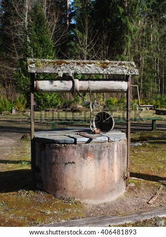 Old water well with bucket in the forest.