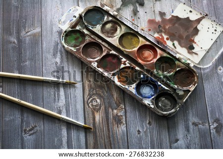 old watercolor paints and brushes - stock photo