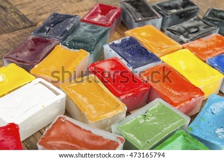 Old watercolor paints on wooden background. Stock image macro.