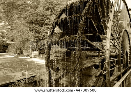 Old waterwheel in the village of Fontaine de Vaucluse (Provence, France). Sepia photo. - stock photo