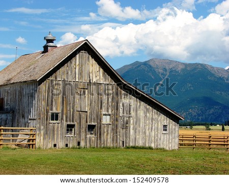 old weathered abandoned building barn in mountains - stock photo