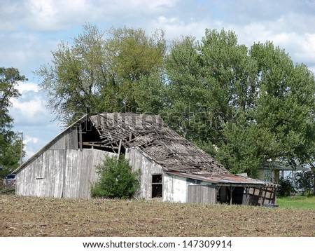 old weathered abandoned farm buildings gray barn in field - stock photo