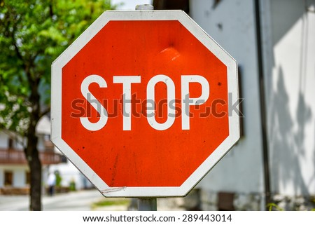 Old, weathered and violated stop sign in the street. Worn out sign with visible damage and dents with houses and street in the background - stock photo