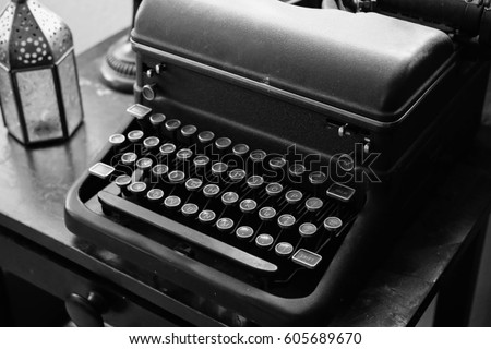 old weathered black and white typewriter sitting on dusty black desk good for any author, writer, journalist or editor. wooden desk provides a vintage design and feel for the aspiring artist.