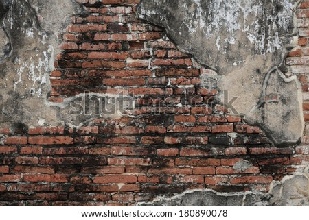 Old weathered brick wall and cement fragment - stock photo