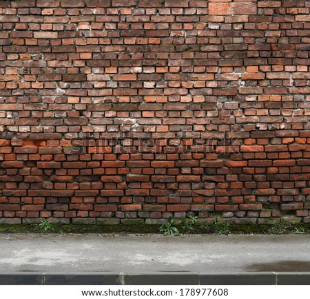old weathered brick wall with sidewalk - stock photo