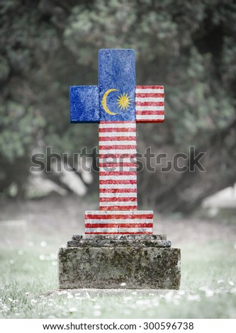 Old weathered gravestone in the cemetery - Malaysia - stock photo