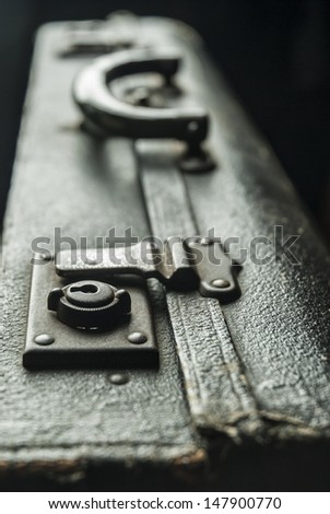 Old, weathered leather suitcase focusing on the lock. - stock photo