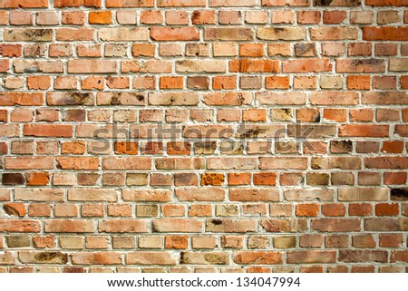 Old weathered red brick wall as background - stock photo