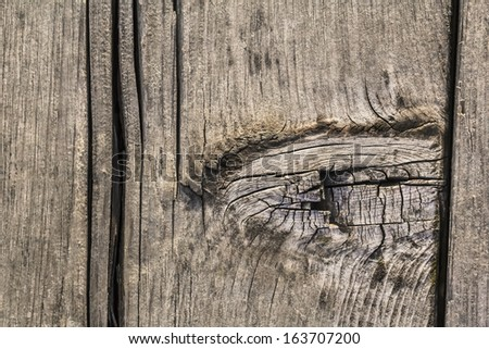 Old, weathered, rotten plank, with large wooden knot, rough surface and lateral cracks parallel to annual growth lines - stock photo