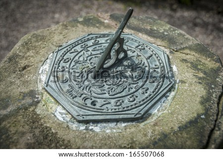 Old weathered stone garden sundial detail. - stock photo